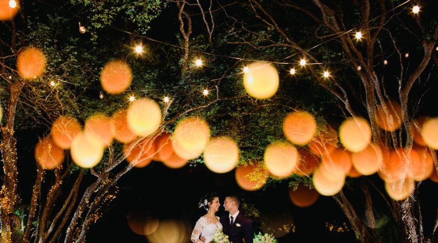 Casal de noivos no altar cercado por luzinhas