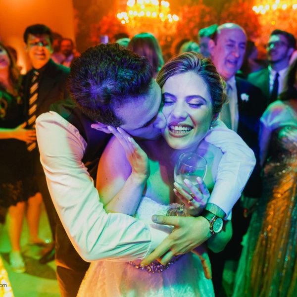 Noivo abraça e beija a noiva em um momento colorido