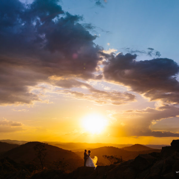 Casal compartilha olhares e momento nas cores incríveis do pôr do sol