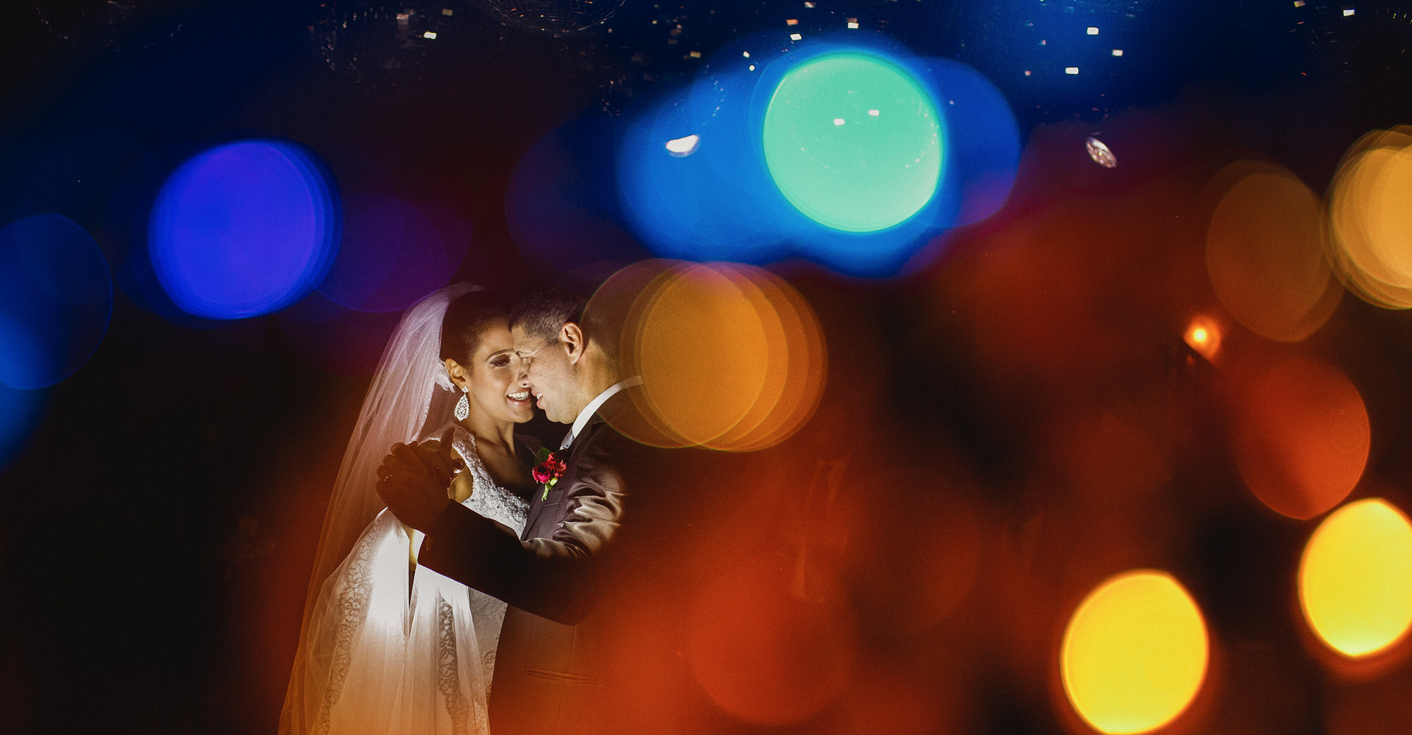 Bride and groom have their first dance surrounded by colorful lights