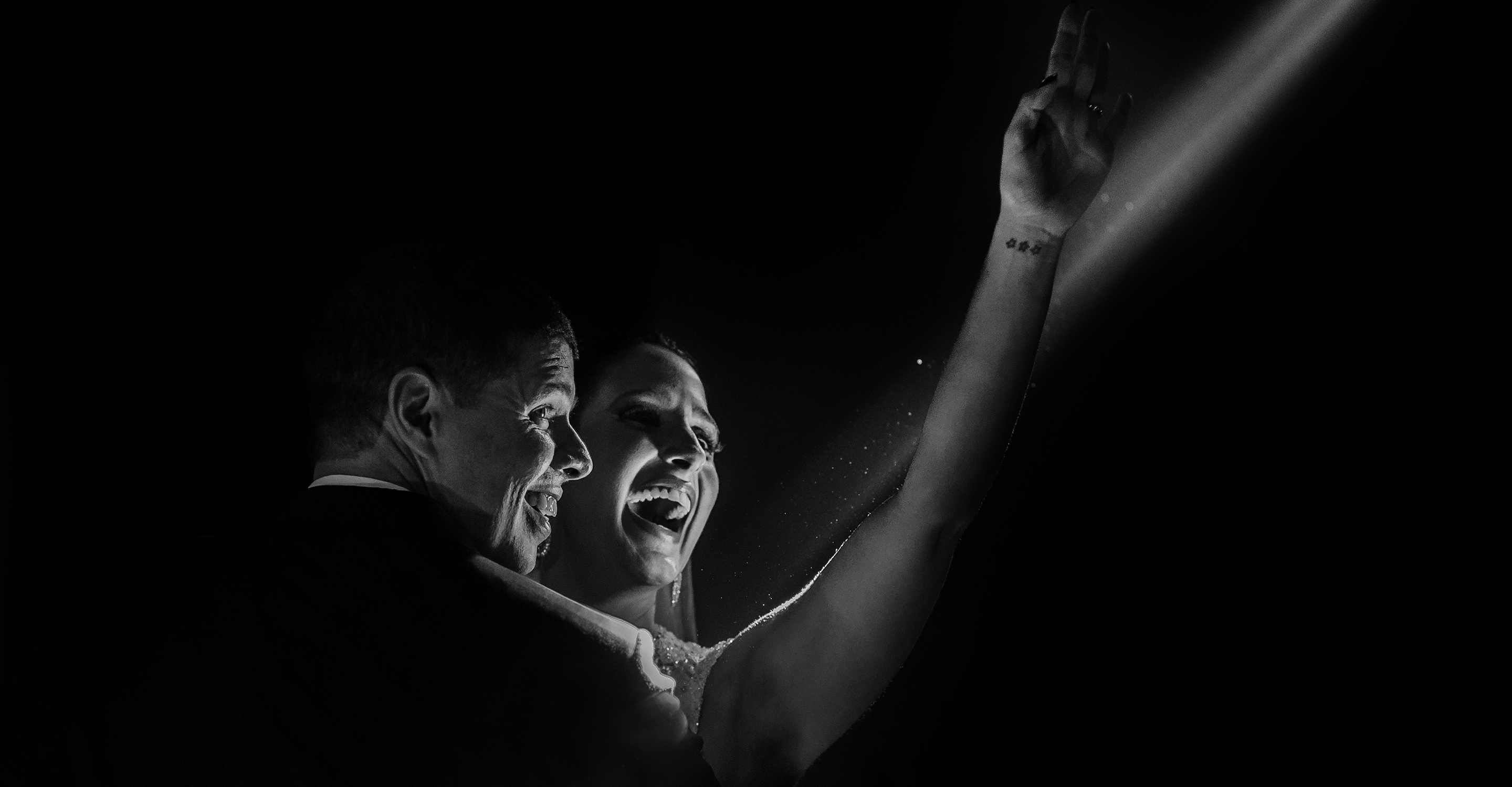 Bride and groom are touched by light in a joyful moment