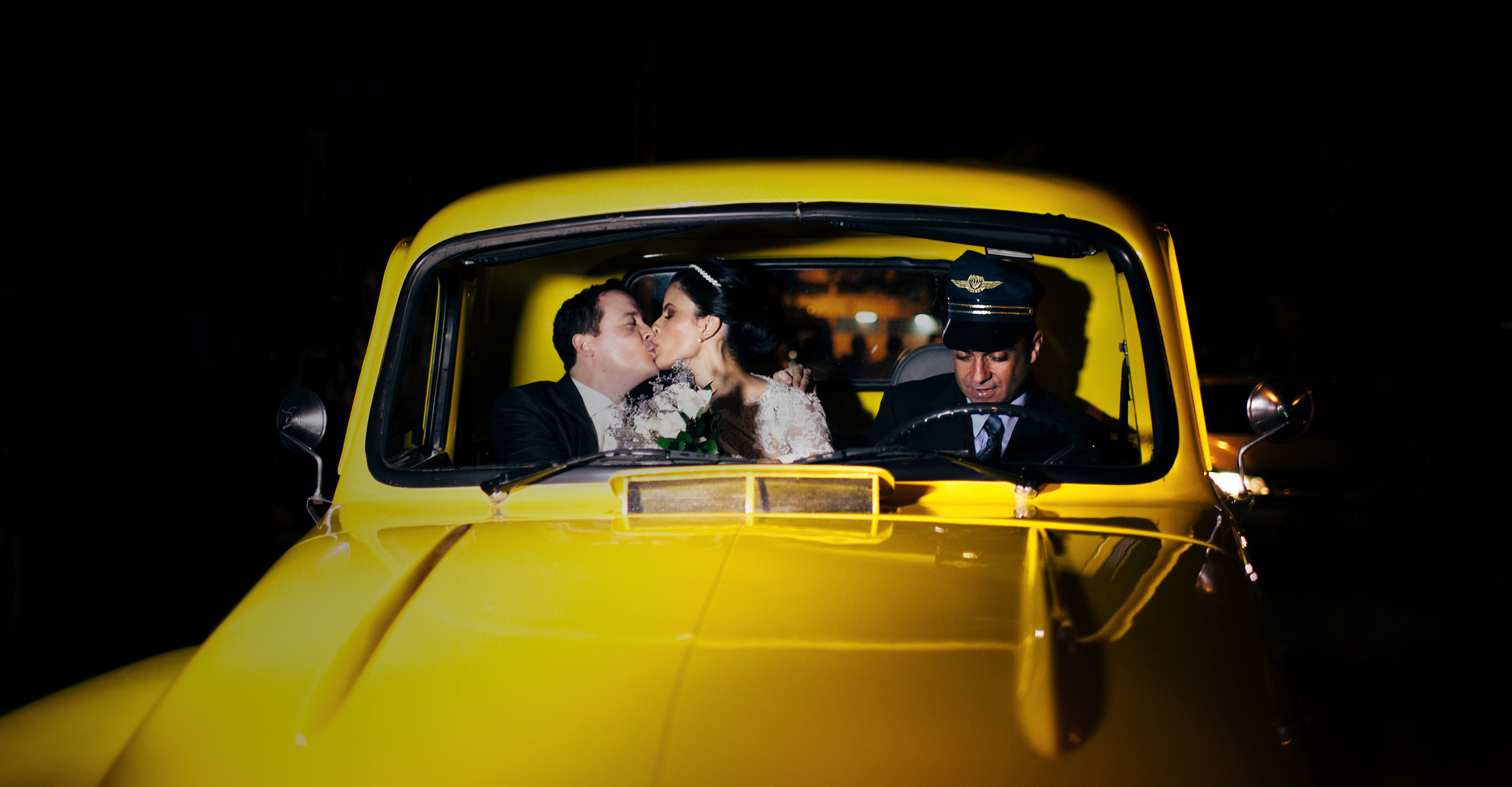 Wedding couple kisses inside a yellow car after the ceremony while the driver is distracted