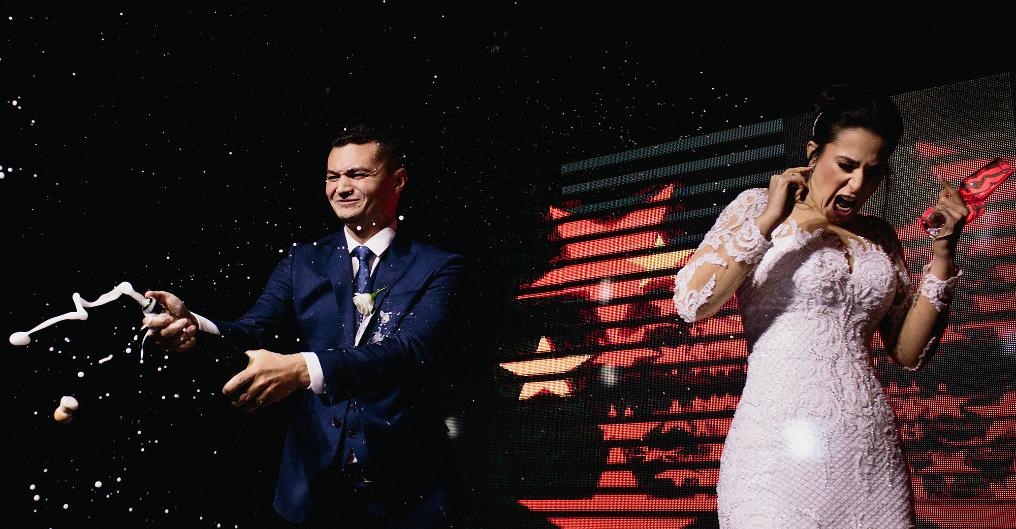 Married couple opening champagne and making a little mess